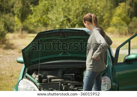 woman with a broken car in a natural outdoor setting