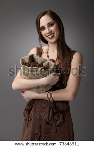 Woman with a burlap sack of coffee beans on gray background