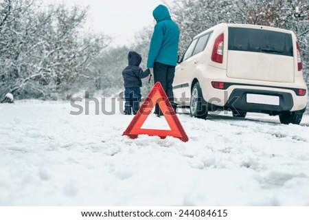 woman with a child on the winter road. emergency sign - stock photo