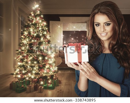 Woman with a Christmas Gift with christmas tree in the background. - stock photo