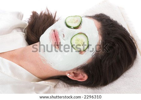 Woman with a claymask on her face and cucumber on her eyelids - stock photo