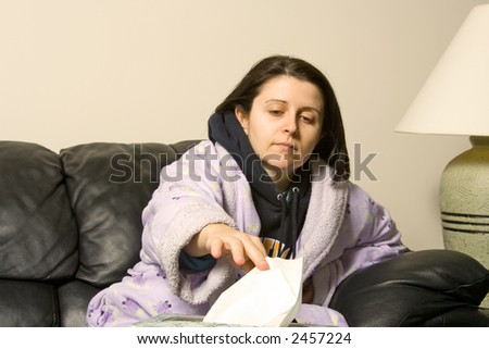 woman with a cold reaching out for a tissue - stock photo