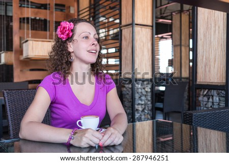 woman with a cup of coffee at a table in a restaurant
