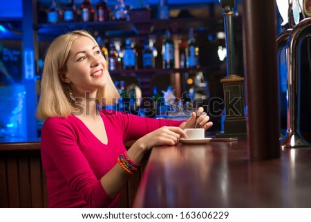 woman with a cup of coffee at the bar