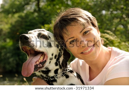 woman with a Dalmatian outdoors - stock photo