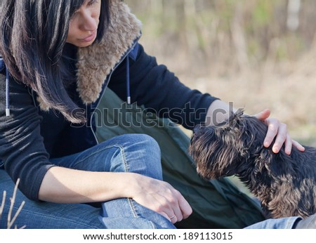 Woman with a dog resting at camp in the forest - stock photo