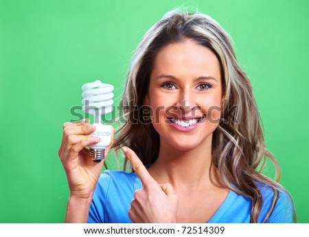 Woman with a fluorescent bulb. Over green background - stock photo