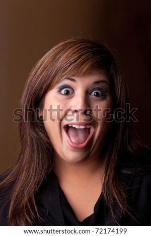 Woman with a funny look on her face smiles over a dark background. - stock photo