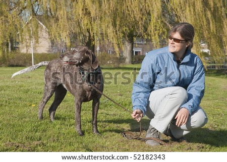Woman with a German Shorthaired Pointer on a leash - stock photo