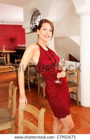 woman with a glass of wine in a restaurant smiling at camera