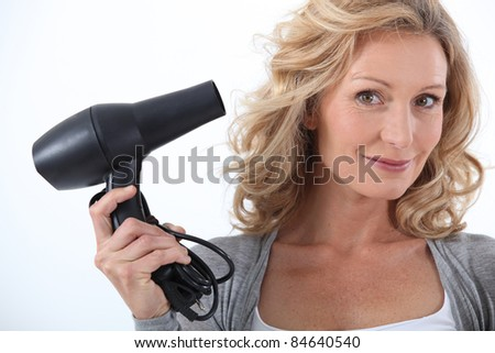 Woman with a hairdryer - stock photo