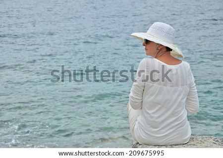 Woman with a hat and sunglasses sitting on the rock near the sea - stock photo