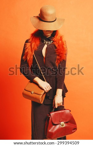 woman with a hat hide her face,elegant dressed and two elegant bags in her hands on a orange background - stock photo