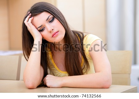 Woman with a headache sitting at home near the table - stock photo