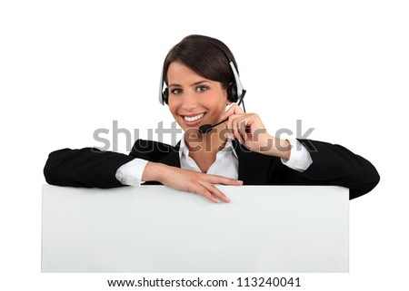 Woman with a headset and a board left blank for your message - stock photo