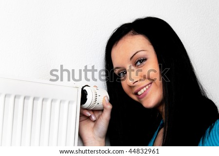 Woman with a heating radiator and thermostat - stock photo