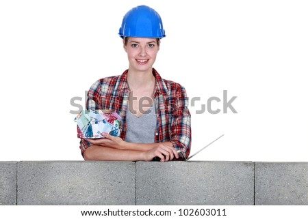 Woman with a house made of money - stock photo