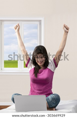 Woman with a laptop rejoicing - stock photo