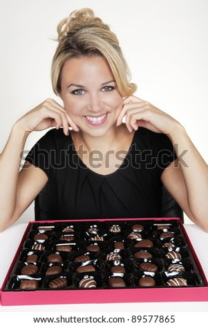 woman with a large box of chocolate and she just eaten one she does not like