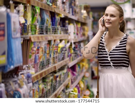 Woman with a long blond ponytail chatting on her mobile while out shopping standing in an aisle in the supermarket - stock photo