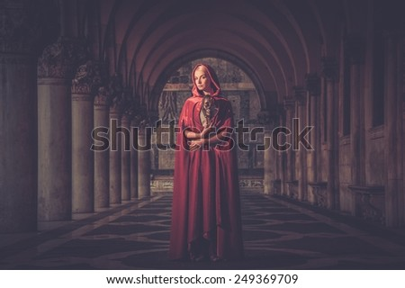Woman with a mask wearing red cloak outdoor - stock photo