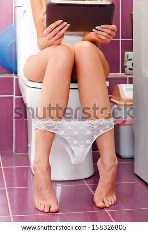 Woman with a mobile computer in the toilet - stock photo