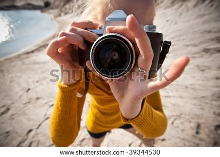 woman with a old camera taking photos in the desert