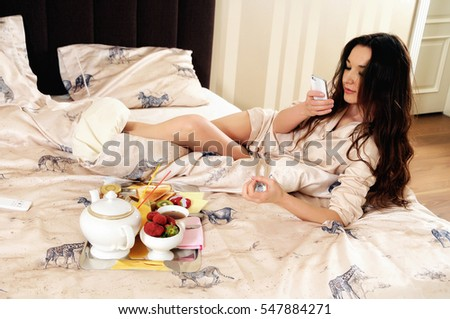 Woman with a phone in bed, photographing her breakfast