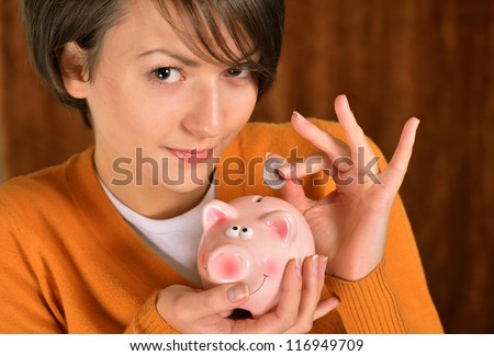 woman with a piggy bank on a brown background - stock photo