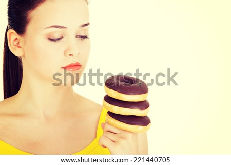 Woman with a pile of doughnuts. Isolated on white. - stock photo
