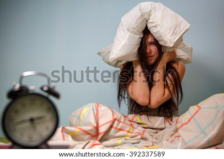 Woman with a pillow over head. - stock photo