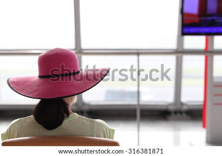 Woman with a pink hat waiting for a flight in the airport terminal  - stock photo