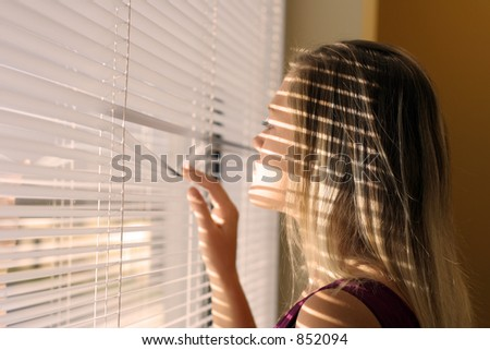 Woman with a shadow from blinds over her face