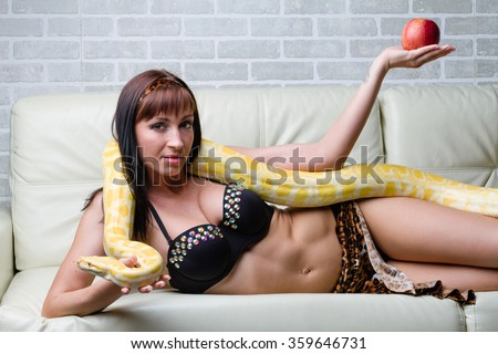Woman with a snake holding red apple on sofa - stock photo