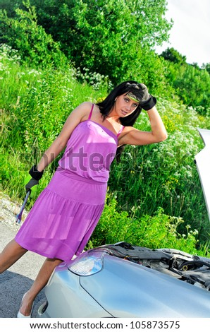 Woman with a stainless steel wrench in hand near broken car. - stock photo