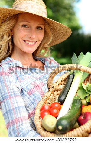 Woman with a straw hat holding basket of vegetables. - stock photo