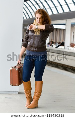 woman with a suitcase looks at the clock while standing on the platform
