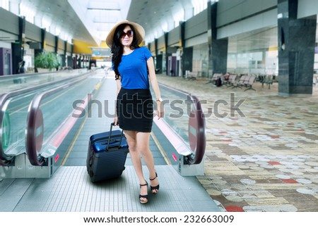 Woman with a suitcase standing in airport - stock photo