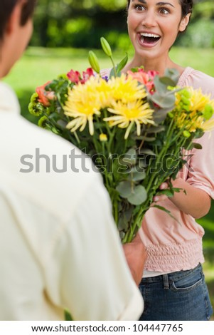 Woman with a surprised expression is presented with a bouquet of flowers by her friend - stock photo
