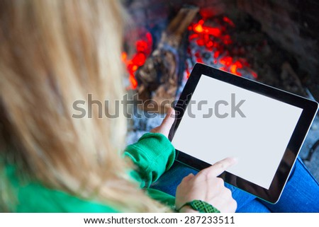 Woman with a tablet fire place and reading - stock photo