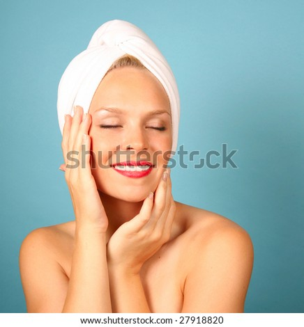 Woman With a Towel on Hair Awaiting Spa Treatment on Teal Background - stock photo