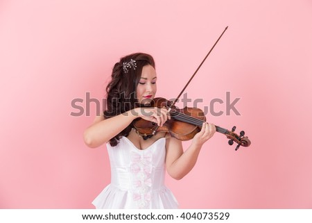 woman with a violin on a pink background - stock photo