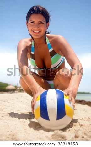 Woman with a volleyball at the beach smiling - stock photo
