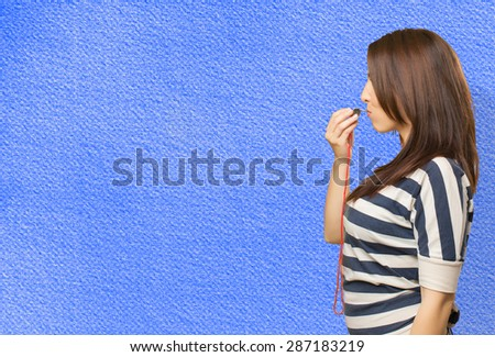 Woman with a whistle. Over blue background - stock photo