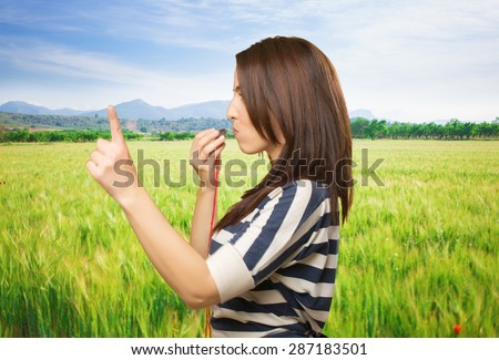 Woman with a whistle pointing with her finger. Over meadow background - stock photo