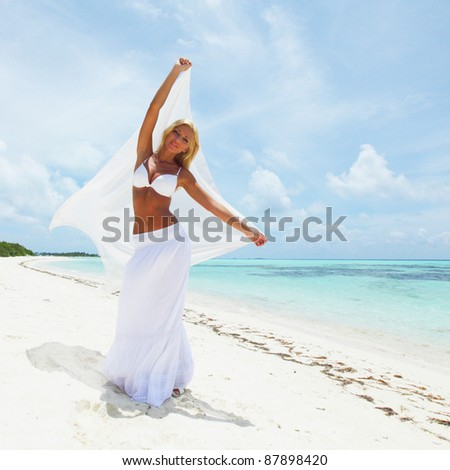woman with a white cloth in his hands on the beach - stock photo