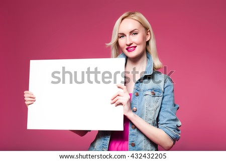 woman with a white sign in the studio. Your text here. Pretty young excited woman holding empty blank board. Colorful studio portrait with pink background.
