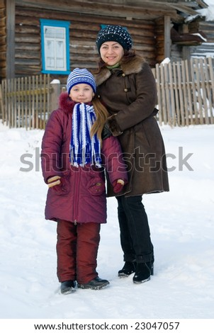 Woman with a young girl in a cap and scarf - stock photo