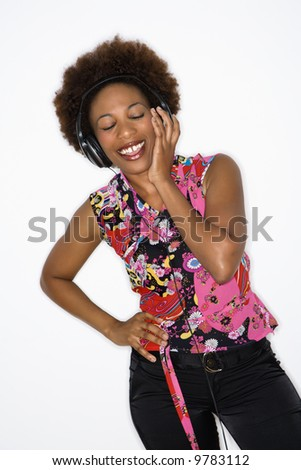 Woman with afro wearing vintage print fabric and listening to headphones smiling.