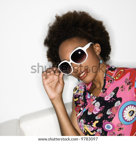 Woman with afro wearing vintage print fabric and oversized sunglasses.